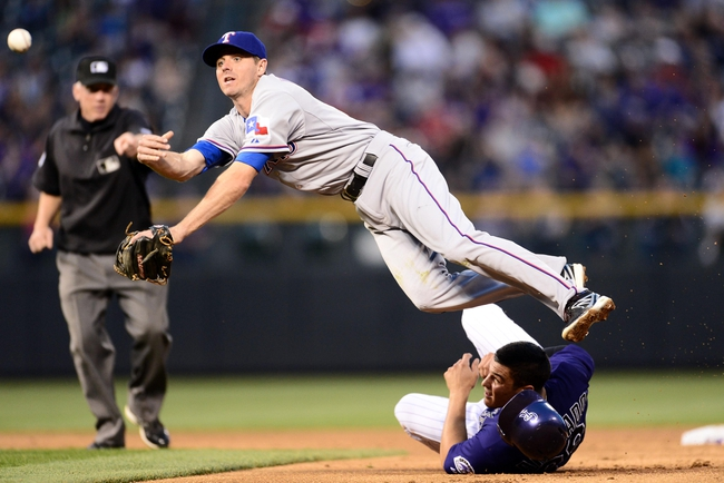 May 5, 2014; Denver, CO, USA; Texas Rangers second baseman Josh Wilson (12) turns a double play over Colorado Rockies third baseman Nolan Arenado (28) in the third inning at Coors Field. Mandatory Credit: Ron Chenoy-USA TODAY Sports