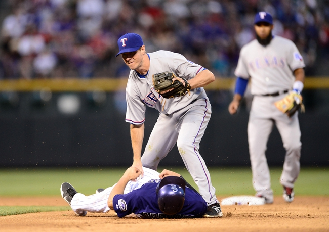 May 5, 2014; Denver, CO, USA; Texas Rangers second baseman Josh Wilson (12) tags out Colorado Rockies third baseman Nolan Arenado (28) in the third inning at Coors Field. Mandatory Credit: Ron Chenoy-USA TODAY Sports