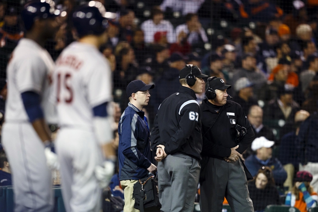 May 5, 2014; Detroit, MI, USA; Umpire Seth Buckminster (62) and umpire Mike Winters (right) look to the scoreboard during a video review in the ninth inning against the Detroit Tigers at Comerica Park. Detroit won 2-0. Mandatory Credit: Rick Osentoski-USA TODAY Sports