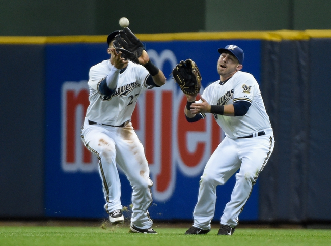 May 5, 2014; Milwaukee, WI, USA;   Milwaukee Brewers center fielder Carlos Gomez (27) catches ball hit by Arizona Diamondbacks third baseman Martin Prado (not pictured) and avoids a collision with left fielder Caleb Gindl (15) in the sixth inning at Miller Park. Mandatory Credit: Benny Sieu-USA TODAY Sports