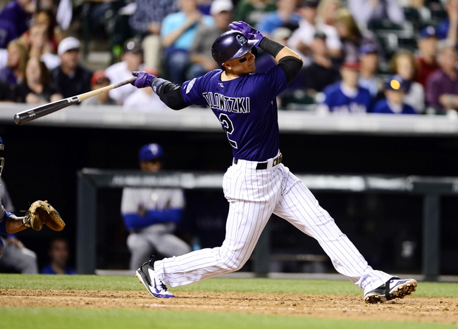 May 5, 2014; Denver, CO, USA; Colorado Rockies shortstop Troy Tulowitzki (2) hits a home run in the seventh inning against the Texas Rangers at Coors Field. Mandatory Credit: Ron Chenoy-USA TODAY Sports