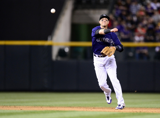 May 5, 2014; Denver, CO, USA; Colorado Rockies shortstop Troy Tulowitzki (2) throws to first base in the seventh inning against the Texas Rangers at Coors Field. Mandatory Credit: Ron Chenoy-USA TODAY Sports