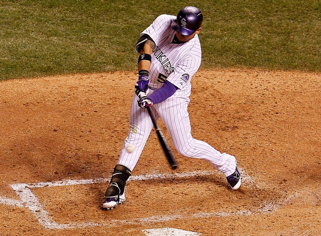 May 6, 2014; Denver, CO, USA; Colorado Rockies left fielder Carlos Gonzalez (5) hits an RBI single in the sixth inning against the Texas Rangers at Coors Field. Mandatory Credit: Isaiah J. Downing-USA TODAY Sports