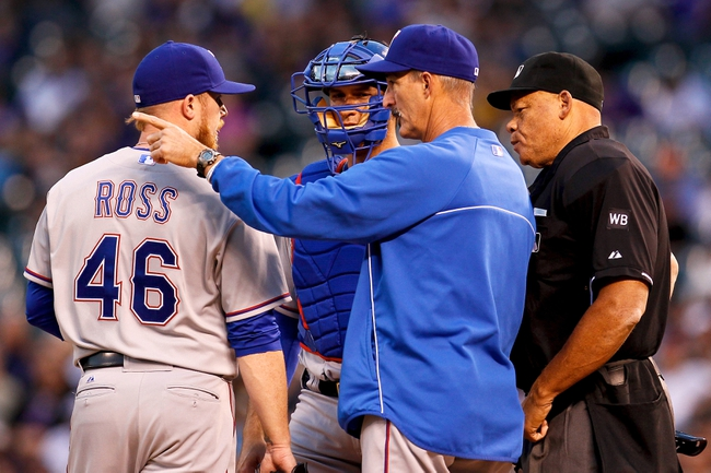 May 6, 2014; Denver, CO, USA; Texas Rangers pitching coach Mike Maddux (31) talks with starting pitcher Robbie Ross (46) and catcher J.P. Arenibia (7) in the third inning against the Colorado Rockies at Coors Field. Mandatory Credit: Isaiah J. Downing-USA TODAY Sports