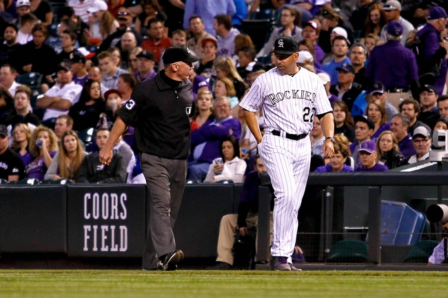 May 6, 2014; Denver, CO, USA; Colorado Rockies manager Walt Weiss (22) calls a challenge with first base umpire Lance Barksdale (23) for a review in the fifth inning against the Texas Rangers at Coors Field. Mandatory Credit: Isaiah J. Downing-USA TODAY Sports