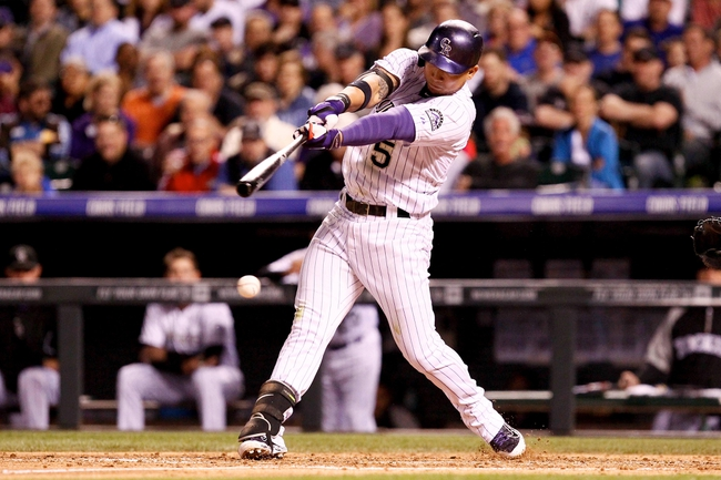 May 6, 2014; Denver, CO, USA; Colorado Rockies left fielder Carlos Gonzalez (5) hits an RBI single in the fifth inning against the Texas Rangers at Coors Field. Mandatory Credit: Isaiah J. Downing-USA TODAY Sports