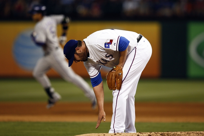 May 7, 2014; Arlington, TX, USA; Texas Rangers starting pitcher Colby Lewis (48) reacts after giving up a solo home run to Colorado Rockies left fielder Carlos Gonzalez (rear) during the fourth inning of a baseball game at Globe Life Park in Arlington. Mandatory Credit: Jim Cowsert-USA TODAY Sports