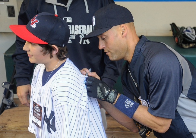 May 9, 2014; Milwaukee, WI, USA;  New York Yankees shortstop Derek Jeter (right) signs an autograph for Matt Thompson before game against the Milwaukee Brewers at Miller Park. Mandatory Credit: Benny Sieu-USA TODAY Sports