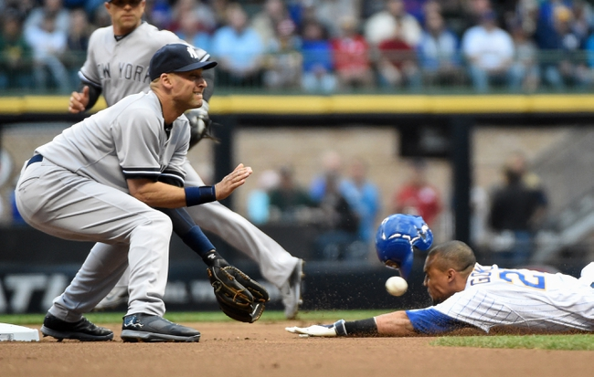 May 9, 2014; Milwaukee, WI, USA;  Milwaukee Brewers center fielder Carlos Gomez (right) steals 2nd bases as the ball gets past New York Yankees shortstop Derek Jeter (left) in the first inning at Miller Park. Mandatory Credit: Benny Sieu-USA TODAY Sports