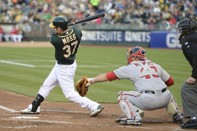 May 9, 2014; Oakland, CA, USA; Oakland Athletics first baseman Brandon Moss (37) hits an RBI-single to score third baseman Josh Donaldson (20, not pictured) in front of Washington Nationals catcher Wilson Ramos (40, right) during the first inning at O.co Coliseum. Mandatory Credit: Kyle Terada-USA TODAY Sports