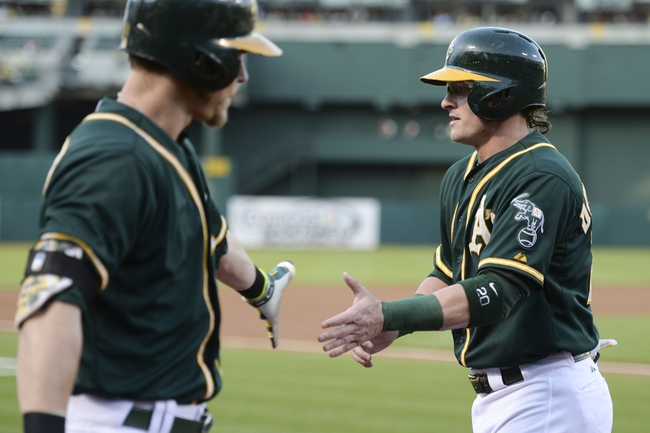 May 9, 2014; Oakland, CA, USA; Oakland Athletics third baseman Josh Donaldson (20, right) is congratulated by right fielder Josh Reddick (16, left) for scoring on a RBI-single by first baseman Brandon Moss (37, not pictured) against the Washington Nationals during the first inning at O.co Coliseum. Mandatory Credit: Kyle Terada-USA TODAY Sports