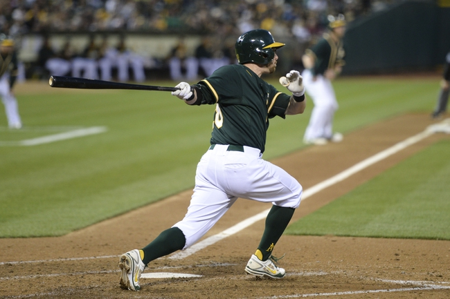 May 9, 2014; Oakland, CA, USA; Oakland Athletics second baseman Eric Sogard (28, front) hits a RBI-single to score right fielder Josh Reddick (16, back) against the Washington Nationals during the fourth inning at O.co Coliseum. Mandatory Credit: Kyle Terada-USA TODAY Sports