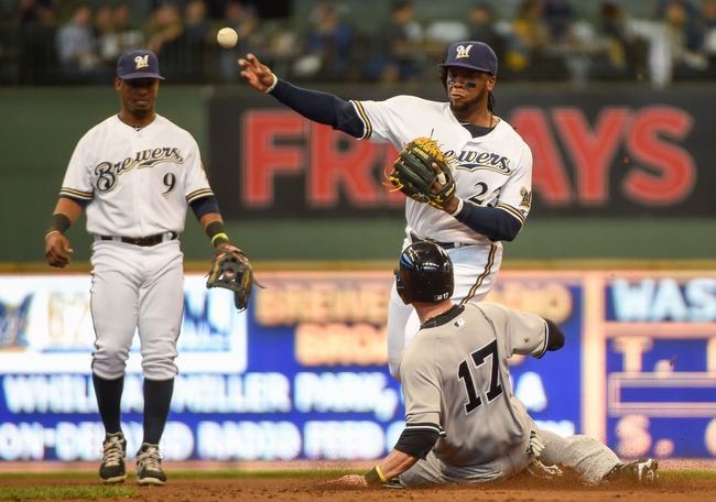 May 10, 2014; Milwaukee, WI, USA;  Milwaukee Brewers second baseman Rickie Weeks (M) completes a double play after forcing out New York Yankees shortstop Brendan Ryan (17) in the third inning at Miller Park. Mandatory Credit: Benny Sieu-USA TODAY Sports
