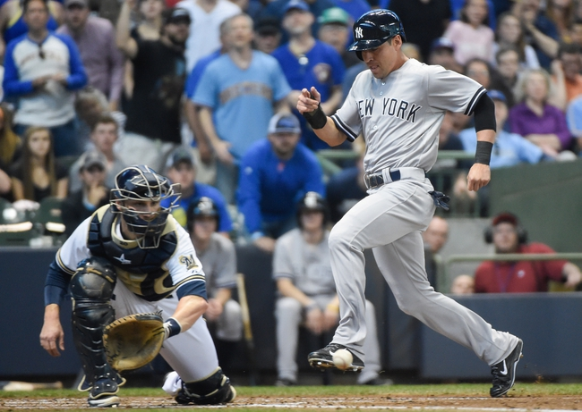 May 10, 2014; Milwaukee, WI, USA;  New York Yankees center fielder Jacoby Ellsbury (22) scores on a triple by left fielder Brett Gardner (not pictured) in front of Milwaukee Brewers catcher Jonathan Lucroy (20) in the third inning at Miller Park. Mandatory Credit: Benny Sieu-USA TODAY Sports