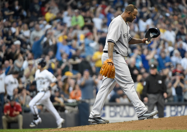 May 10, 2014; Milwaukee, WI, USA;  New York Yankees pitcher CC Sabathia (R) reacts after giving up a 2-run home run to Milwaukee Brewers catcher Jonathan Lucroy (L) in the third inning at Miller Park. Mandatory Credit: Benny Sieu-USA TODAY Sports