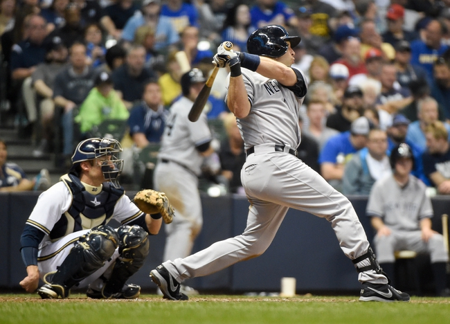 May 10, 2014; Milwaukee, WI, USA; New York Yankees first baseman Mark Teixeira (R) hits a solo home run in the sixth inning as Milwaukee Brewers catcher Jonathan Lucroy (L) watches at Miller Park. Mandatory Credit: Benny Sieu-USA TODAY Sports