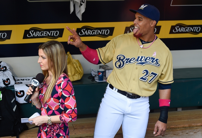 May 11, 2014; Milwaukee, WI, USA; Milwaukee Brewers center fielder Carlos Gomez (27) photobombs Fox Sports reporter Sophia Minnaert (L) prior to the game against the New York Yankees at Miller Park. Mandatory Credit: Benny Sieu-USA TODAY Sports