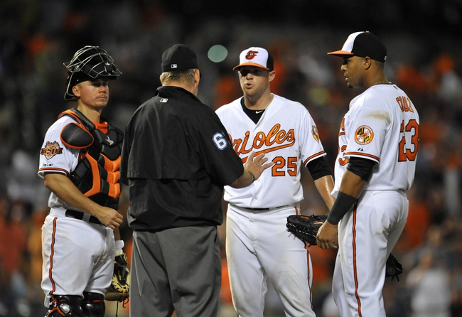 May 12, 2014; Baltimore, MD, USA; Baltimore Orioles starting pitcher Bud Norris (25) is ejected from the game by home plate umpire James Hoye (92) after hitting Detroit Tigers right fielder Torii Hunter (not shown) with a pitch in the eighth inning at Oriole Park at Camden Yards. The Tigers defeated the Orioles 4-1. Mandatory Credit: Joy R. Absalon-USA TODAY Sports