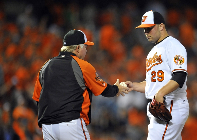May 13, 2014; Baltimore, MD, USA; Baltimore Orioles pitcher Tommy Hunter (29) is pulled from the game by manager Buck Showalter (26) after  giving up the game winning home run in the ninth inning against the Detroit Tigers at Oriole Park at Camden Yards. The Tigers defeated the Orioles 4-1. Mandatory Credit: Joy R. Absalon-USA TODAY Sports