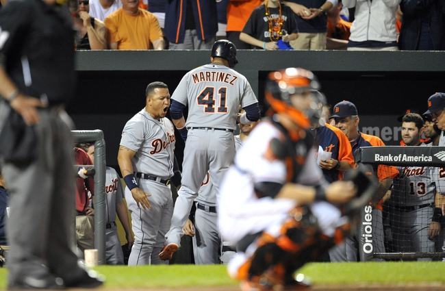 May 13, 2014; Baltimore, MD, USA; Detroit Tigers first baseman Miguel Cabrera (24) reacts as Victor Martinez (41) enters the dugout after hitting a solo home run in the ninth inning against the Baltimore Orioles at Oriole Park at Camden Yards. The Tigers defeated the Orioles 4-1. Mandatory Credit: Joy R. Absalon-USA TODAY Sports