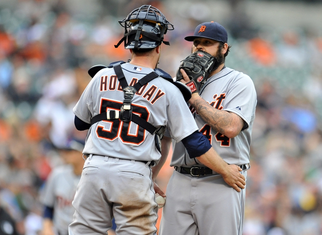 May 14, 2014; Baltimore, MD, USA; Detroit Tigers catcher Bryan Holaday (50) goes out to the mound to talk to pitcher Joba Chamberlain (44) in the eighth inning against the Baltimore Orioles at Oriole Park at Camden Yards. The Tigers defeated the Orioles 7-5 completing the three game sweep. Mandatory Credit: Joy R. Absalon-USA TODAY Sports
