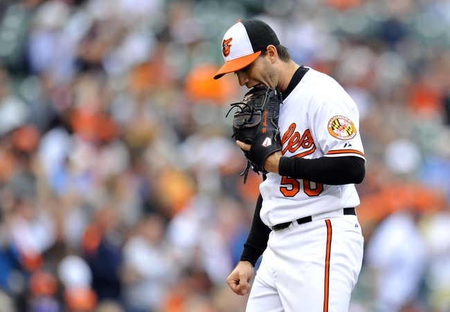 May 14, 2014; Baltimore, MD, USA; Baltimore Orioles pitcher Miguel Gonzalez (50) reacts after giving up a home run to Detroit Tigers left fielder Rajai Davis (not shown) in the sixth inning at Oriole Park at Camden Yards. The Tigers defeated the Orioles 7-5 completing the three game sweep. Mandatory Credit: Joy R. Absalon-USA TODAY Sports