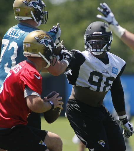 May 16, 2014; Jacksonville, FL, USA; Jacksonville Jaguars defensive end Chris Smith (98) tries to get to quarterback Blake Bortles (5) but is blocked by tackle Josh Wells (73) during rookie minicamp at Florida Blue Health and Wellness Practice Fields. Mandatory Credit: Phil Sears-USA TODAY Sports