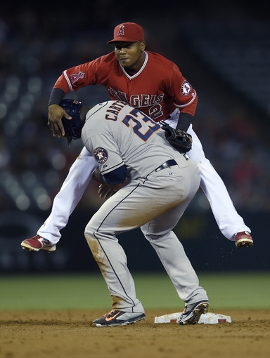 May 19, 2014; Anaheim, CA, USA; Houston Astros designated hitter Chris Carter (23) runs into Los Angeles Angels short stop Erick Aybar (2) after being forced out at second for a double play during the third inning at Angel Stadium of Anaheim. Mandatory Credit: Kelvin Kuo-USA TODAY Sports