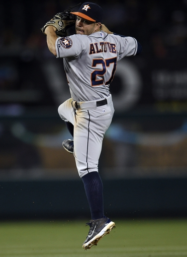 May 19, 2014; Anaheim, CA, USA; Houston Astros second baseman Jose Altuve (27) jumps up to throw the ball to first during the eighth inning against the Los Angeles Angels at Angel Stadium of Anaheim. The Houston Astros won 6-2. Mandatory Credit: Kelvin Kuo-USA TODAY Sports