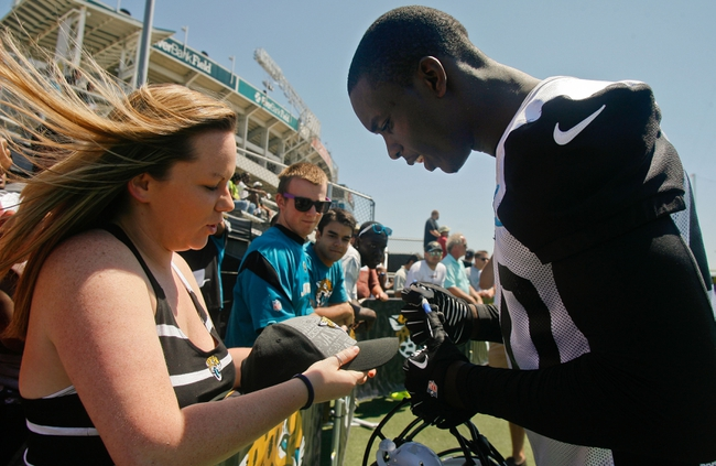 May 16, 2014; Jacksonville, FL, USA; At rioght, Jacksonville Jaguars linebacker Telvin Smith (50) signs an autograph for a fan during Rookie Minicamp at Florida Blue Health and Wellness Practice Fields. Mandatory Credit: Phil Sears-USA TODAY Sports
