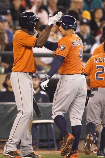 May 25, 2014; Seattle, WA, USA; Houston Astros right fielder George Springer (4) is greeted by Houston Astros center fielder Dexter Fowler (21) in the on deck circle after hitting a two-run homer against the Seattle Mariners during the sixth inning at Safeco Field. Mandatory Credit: Joe Nicholson-USA TODAY Sports