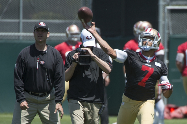 May 28, 2014; Santa Clara, CA, USA; San Francisco 49ers head coach Jim Harbaugh (left) watches quarterback Colin Kaepernick (7) pass the football during organized team activities at the SAP Performance Facility. Mandatory Credit: Kyle Terada-USA TODAY Sports