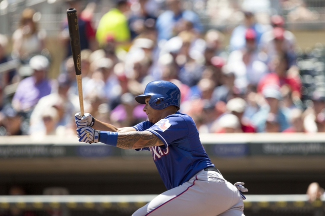 May 29, 2014; Minneapolis, MN, USA; Texas Rangers left fielder Michael Choice (15) hits a single in the second inning against the Minnesota Twins at Target Field. Mandatory Credit: Jesse Johnson-USA TODAY Sports