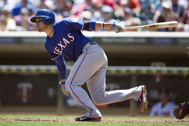 May 29, 2014; Minneapolis, MN, USA; Texas Rangers catcher Robinson Chirinos (61) hits a RBI double in the sixth inning against the Minnesota Twins at Target Field. Mandatory Credit: Jesse Johnson-USA TODAY Sports
