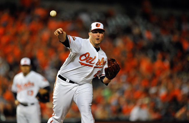 May 13, 2014; Baltimore, MD, USA; Baltimore Orioles pitcher Tommy Hunter (29) attempts a pick off in the ninth inning against the Detroit Tigers at Oriole Park at Camden Yards. The Tigers defeated the Orioles 4-1. Mandatory Credit: Joy R. Absalon-USA TODAY Sports