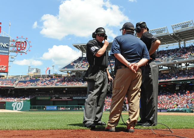 Jun 1, 2014; Washington, DC, USA; Umpires Clint Fagan (left) and Jeff Nelson (right) review challenges by both the Washington Nationals and Texas Rangers during the first inning at Nationals Park. Mandatory Credit: Brad Mills-USA TODAY Sports