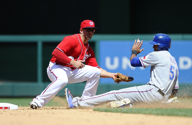 Jun 1, 2014; Washington, DC, USA; Texas Rangers right fielder Alex Rios (51) steal second base as Washington Nationals second baseman Danny Espinosa (8) is unable to apply the tag during the sixth inning at Nationals Park. The Rangers won 2-0. Mandatory Credit: Brad Mills-USA TODAY Sports