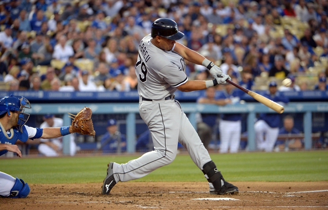 Jun 2, 2014; Los Angeles, CA, USA; Chicago White Sox first baseman Jose Abreu (79) follows through on a two-run home run in the fourth inning as Los Angeles Dodgers catcher Drew Butera (31) watches at Dodger Stadium. Mandatory Credit: Kirby Lee-USA TODAY Sports