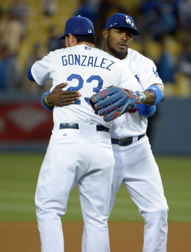 Jun 2, 2014; Los Angeles, CA, USA; Los Angeles Dodgers first baseman Adrian Gonzalez (23) and right fielder Yasiel Puig (66) embrace at the end of the game against the Chicago White Sox at Dodger Stadium. The Dodgers defeated the White Sox 5-2. Mandatory Credit: Kirby Lee-USA TODAY Sports