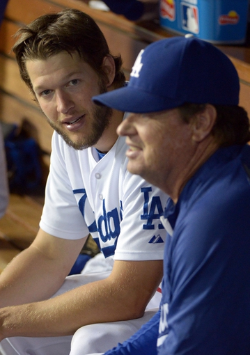 Jun 2, 2014; Los Angeles, CA, USA; Los Angeles Dodgers pitcher Clayton Kershaw (left) and pitching coach Rick Honeycutt watch in the dugout in the ninth inning against the Chicago White Sox at Dodger Stadium. The Dodgers defeated the White Sox 5-2. Mandatory Credit: Kirby Lee-USA TODAY Sports
