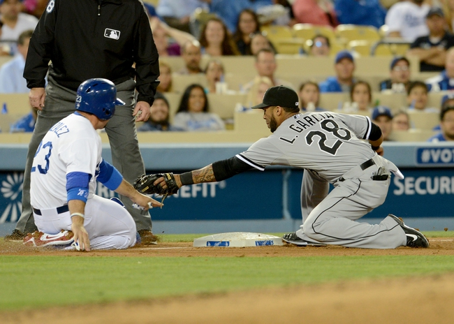 Jun 4, 2014; Los Angeles, CA, USA; Chicago White Sox second baseman Leury Garcia (28) reaches for the tag as Los Angeles Dodgers first baseman Adrian Gonzalez (23) is called safe at third base by umpire Gary Cederstrom (38) in the fourth inning of the game at Dodger Stadium. The call was overturned after a review of the play.  Mandatory Credit: Jayne Kamin-Oncea-USA TODAY Sports
