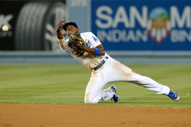 Jun 4, 2014; Los Angeles, CA, USA; Los Angeles Dodgers second baseman Dee Gordon (9) throws to first after a dive for a ball hit by Chicago White Sox starting pitcher John Danks (50) in the sixth inning of the game at Dodger Stadium. Mandatory Credit: Jayne Kamin-Oncea-USA TODAY Sports