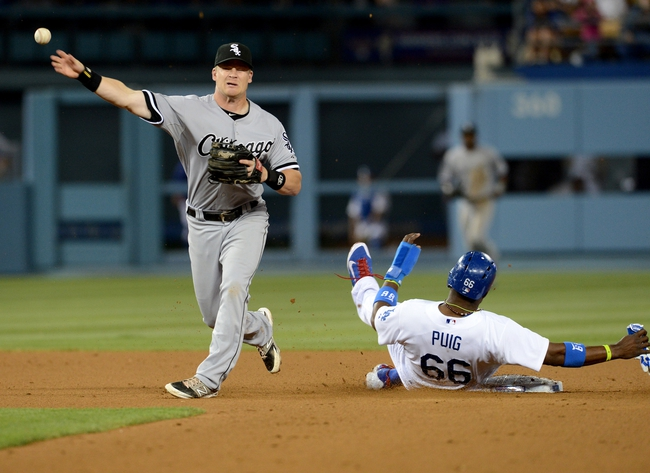 Jun 4, 2014; Los Angeles, CA, USA; Chicago White Sox second baseman Gordon Beckham (15) throws to first as Los Angeles Dodgers right fielder Yasiel Puig (66) breaks up a double play in the eighth inning of the game at Dodger Stadium. White Sox won 2-1. Mandatory Credit: Jayne Kamin-Oncea-USA TODAY Sports