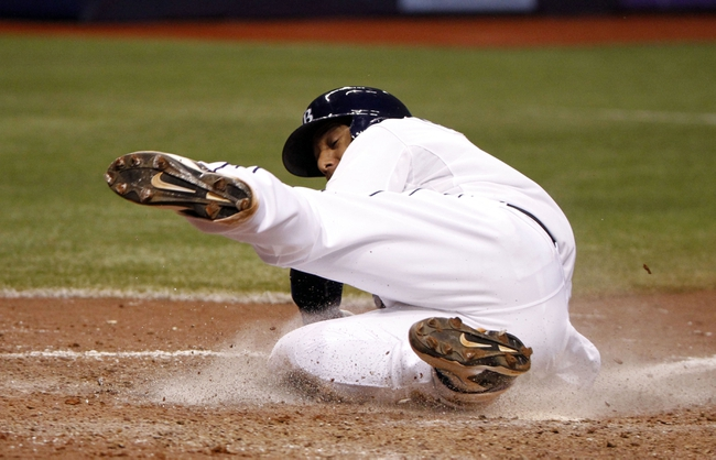 Jun 6, 2014; St. Petersburg, FL, USA; Tampa Bay Rays shortstop Yunel Escobar (11) sides home and he scored during the seventh inning against the Seattle Mariners at Tropicana Field. Tampa Bay Rays defeated the Seattle Mariners 4-0. Mandatory Credit: Kim Klement-USA TODAY Sports