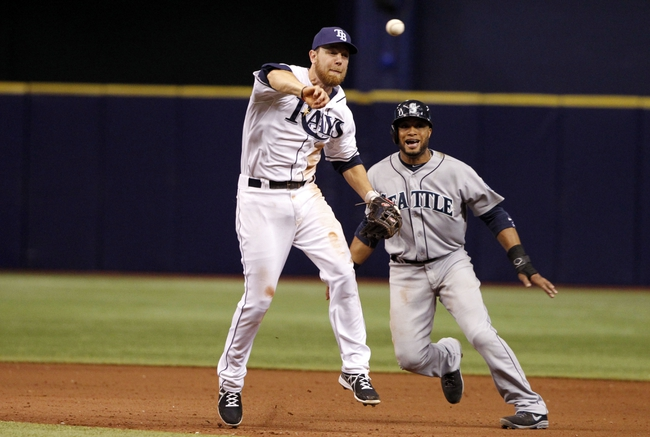 Jun 6, 2014; St. Petersburg, FL, USA; Seattle Mariners second baseman Robinson Cano (22) runs by Tampa Bay Rays second baseman Ben Zobrist (18) as he throws the ball to first for an out during the ninth inning at Tropicana Field. Tampa Bay Rays defeated the Seattle Mariners 4-0. Mandatory Credit: Kim Klement-USA TODAY Sports