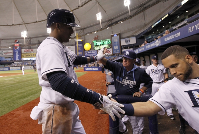 Jun 6, 2014; St. Petersburg, FL, USA; Tampa Bay Rays shortstop Yunel Escobar (11) is congratulated by manager Joe Maddon (70) and first baseman James Loney (21) after he scored during the seventh inning against the Seattle Mariners  at Tropicana Field. Tampa Bay Rays defeated the Seattle Mariners 4-0. Mandatory Credit: Kim Klement-USA TODAY Sports