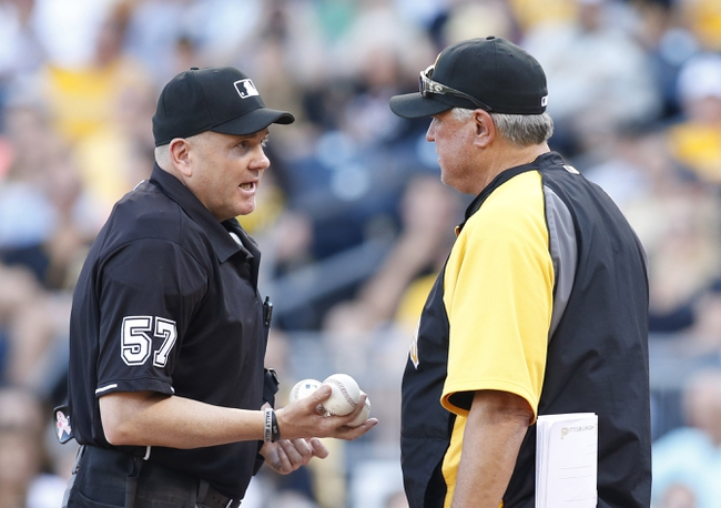 Jun 7, 2014; Pittsburgh, PA, USA; Home plate umpire Mike Everitt (57) talks with Pittsburgh Pirates manager Clint Hurdle (right) against the Milwaukee Brewers during the eighth inning at PNC Park. The Brewers won 9-3. Mandatory Credit: Charles LeClaire-USA TODAY Sports