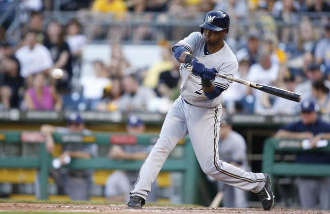 Jun 7, 2014; Pittsburgh, PA, USA; Milwaukee Brewers third baseman Irving Falu (21) hits a sacrifice fly RBI against the Pittsburgh Pirates during the eighth inning at PNC Park. The Brewers won 9-3. Mandatory Credit: Charles LeClaire-USA TODAY Sports