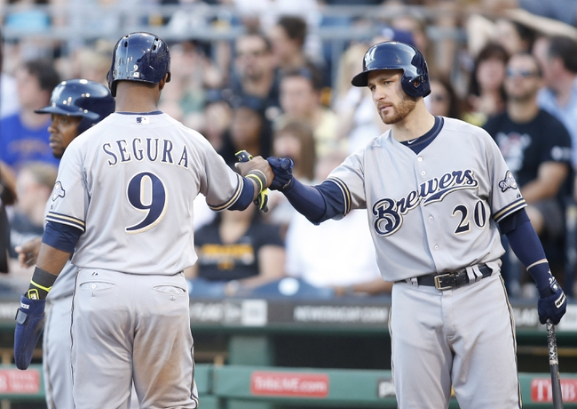 Jun 7, 2014; Pittsburgh, PA, USA; Milwaukee Brewers shortstop Jean Segura (9) is greeted at home plate by catcher Jonathan Lucroy (20) after Segura scored a run against the Pittsburgh Pirates during the eighth inning at PNC Park. The Brewers won 9-3. Mandatory Credit: Charles LeClaire-USA TODAY Sports