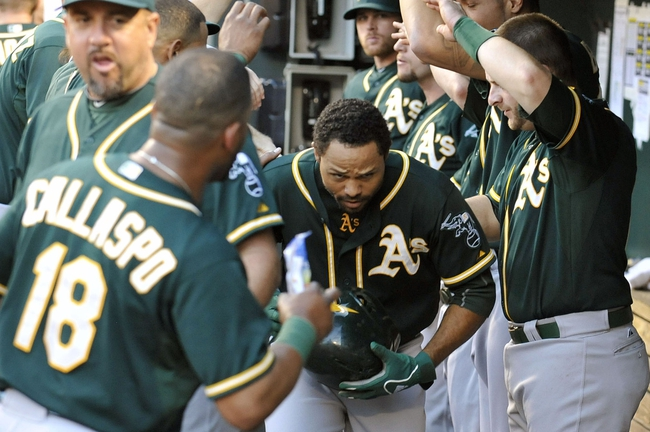 Jun 7, 2014; Baltimore, MD, USA; Oakland Athletics center fielder Coco Crisp (4) is congratulated by teammates after hitting a solo home run in the third inning against the Baltimore Orioles at Oriole Park at Camden Yards. Mandatory Credit: Joy R. Absalon-USA TODAY Sports